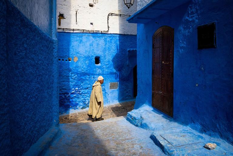 Chefchaouen, Morocco - April 10, 2016: An old man walking in a street of the town of Chefchaouen in Morocco.