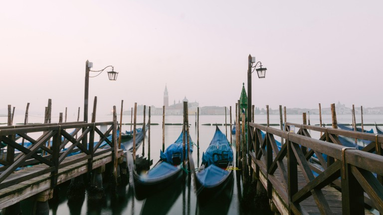 Gondolas, the traditional flat-bottomed Venetian rowing boats, at their moorings in San Marco Square at sunrise, with the lagoon and the church of San
