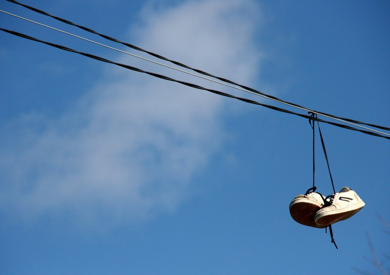 Shoes hanging from a wire │© Edward Morgan / Flickr