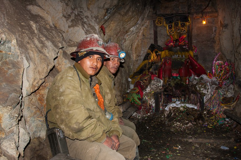 Miners are resting underground the mine, praying in front of their Patron Saint and bring in offer cigarettes, beer and coca leaves © Paolo Arsie Pelanda / Shutterstock