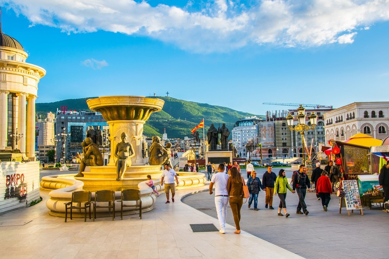 People are passing over the ancient stone bridge in the macedonian capital skopje leading to the macedonia square © trabantos / Shutterstock