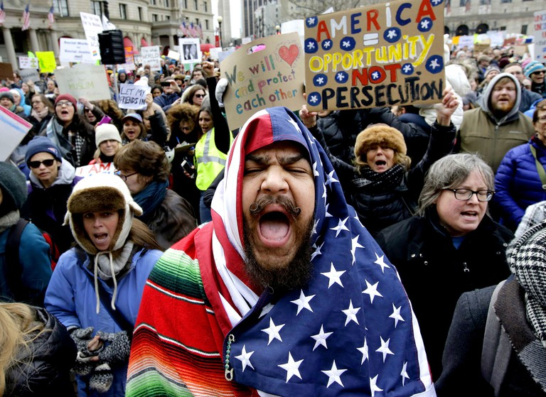 Izzy Berdan, of Boston, center, wears an American flags as he chants slogans with other demonstrators © AP/REX/Shutterstock