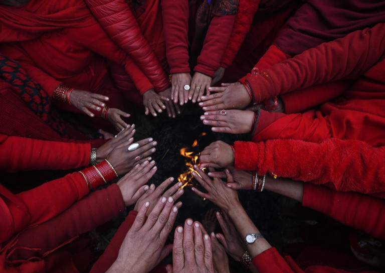 A group of Nepalese Hindu devotees warm themselves after taking holy bath © NARENDRA SHRESTHA/EPA/REX/Shutterstock