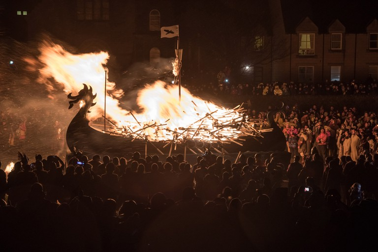 The galley Falcon is set ablaze by the guizers flaming torches | © Austin Taylor / VisitScotland