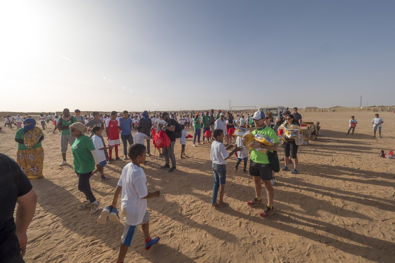 Volunteers handing bags and clothes to children after the 2017 Sahara Marathon | © Flickr/Sahara Marathon