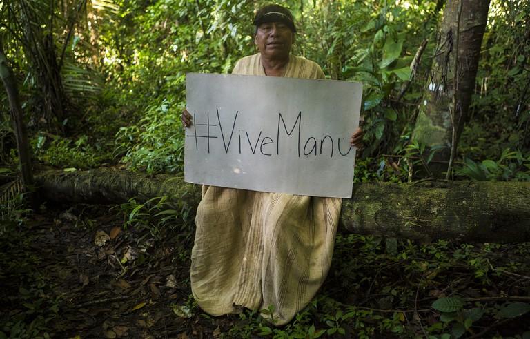 Mateo, a Matsiguenka curandero (shaman), in a cushma tunic holding a sign that promotes the Manu's ecological importance.|©Manuel Orbegozo/WWF Perú