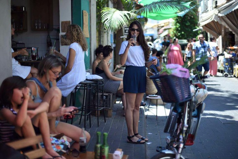 Tel Avivians drink coffee on a weekday at Cafe Yom Tov