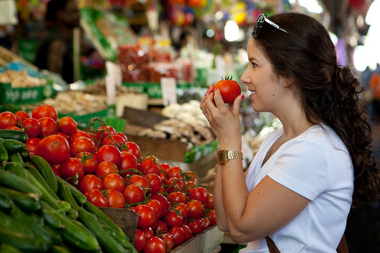 A young woman enjoys Israel's best fruit (yup, it's not a vegetable!) at Tel Aviv's Carmel Market.