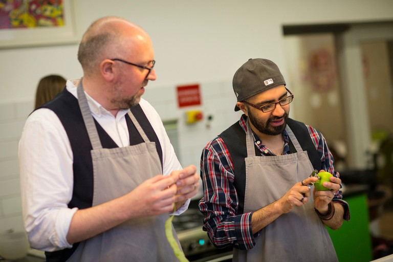 Andrew Webb guides Cassam Looch through the tricky task of peeling an apple.