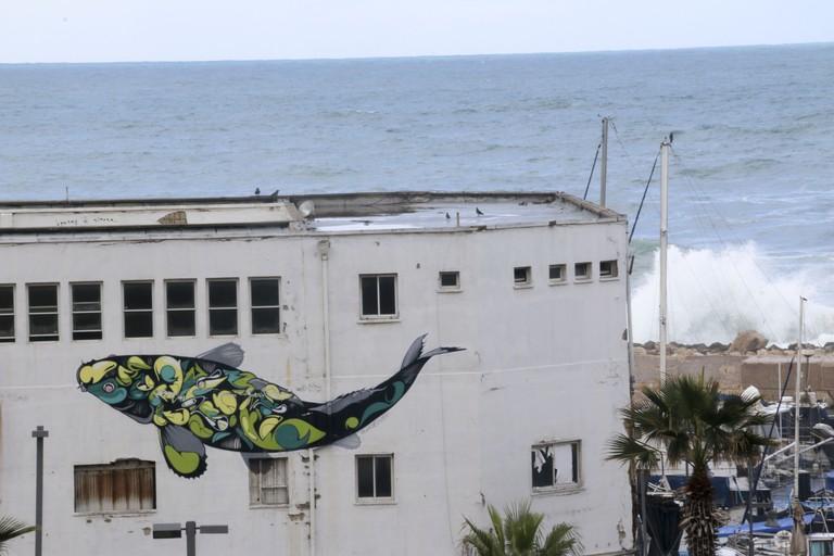 Waves break behind a giant graffiti mural in Jaffa's Old Port | Ami Zoran, courtesy