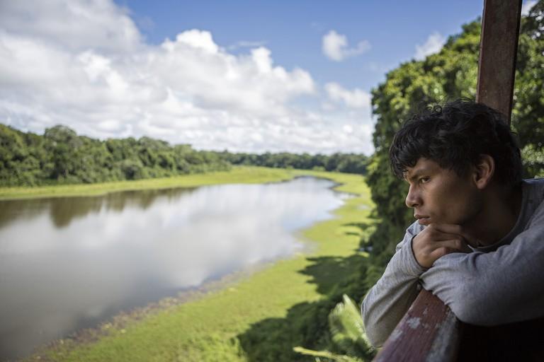 Linder, a crew member and a Yine native, contemplates cocha (lagoon) Otorongo. |©Manuel Orbegozo/WWF Perú