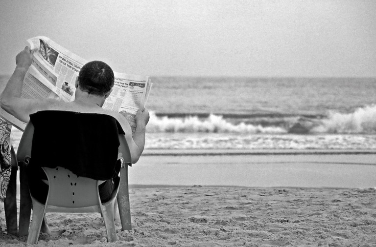 Man sits on one of Tel Aviv's beach reading a newspaper, 'cause that's what's the beach is for of you can go everyday