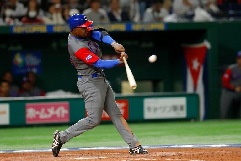 Alexander Ayala of Team Cuba hits sac fly against Japan | © Yuki Taguchi/WBCI/MLB Photos via Getty Images