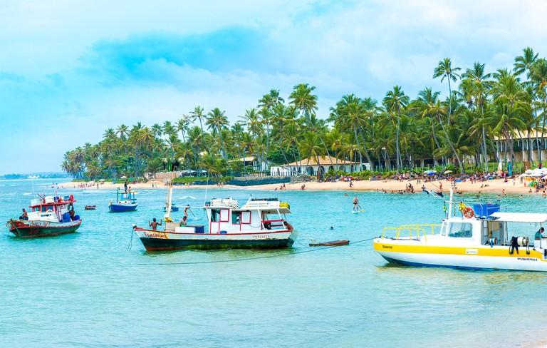 People enjoy a sunny day at Praia do Forte (Forte Beach) in Bahia, Brazil  © Filipe Frazao/Shutterstock