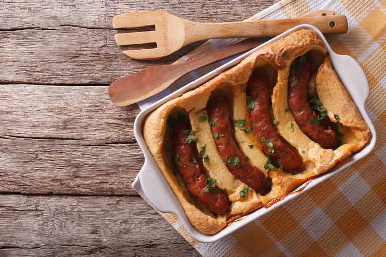 Toad in the hole into a baking dish on the table. Horizontal top view | © AS Food studio / Shutterstock