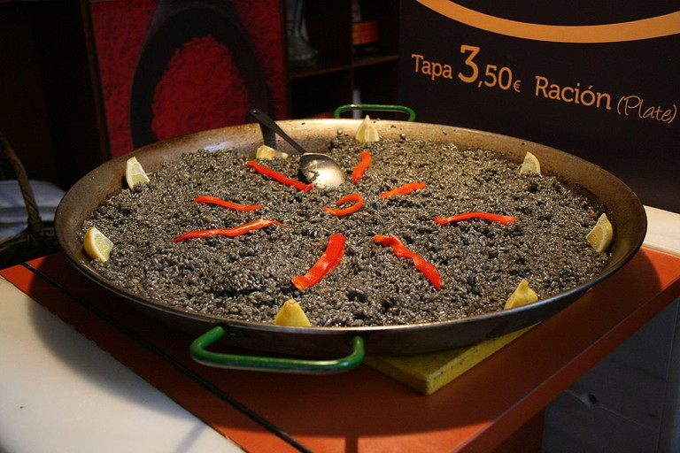 """<a href=""""https://upload.wikimedia.org/wikipedia/commons/2/2f/Arroz_negro_-_SM.JPG""""><i>Arròs negre</i>, coloured with squid ink   © Wikimedia Commons</a>"""