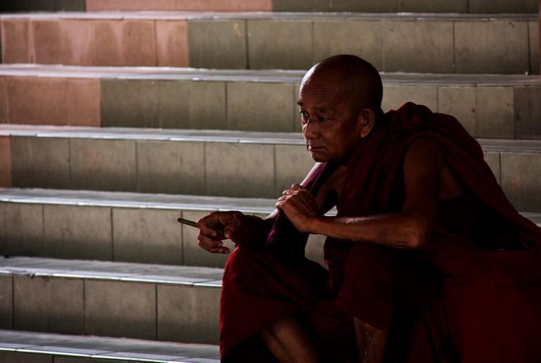 A monk smoking a cigar