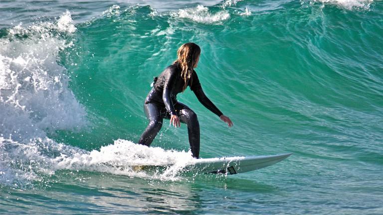A woman riding a wave at Costa da Caparica © João Trindade / Flickr