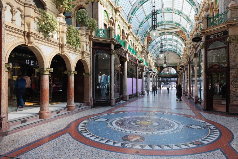 Floor mosaic and traditional upmarket designer shops in County Arcade in Victoria Quarter shopping centre in Leeds Yorkshire England UK Britain