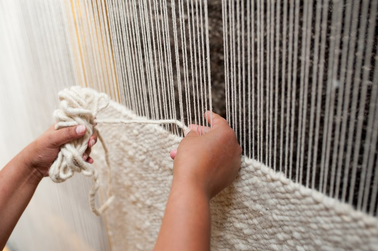 Weaving a rug by hand on a traditional loom © Courtesy of Coral and Hive