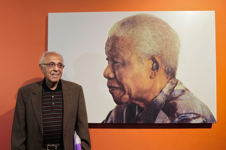 Ahmed Kathrada poses in front of his Nelson Mandela's portrait