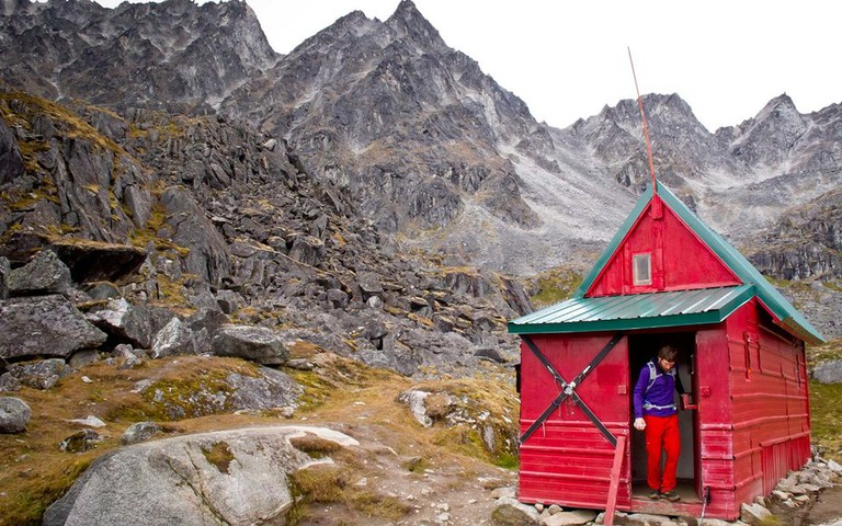 Man Standing In The Doorway Of Mint Hut, Talkeetna Mountains Near Hatcher Pass, Southcentral Alaska, Autumn