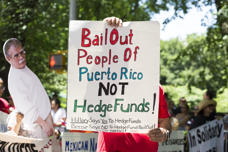 A marcher displays the political message Bail Out People of Puerto Rico Not Hedge Funds in the 59th National Puerto Rican Day Parade on 5th Ave in New York City June 12 2016 | © Glynnis Jones/ Shutterstock