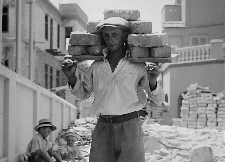 A worker carries bricks to build the first Hebrew city, Tel Aviv