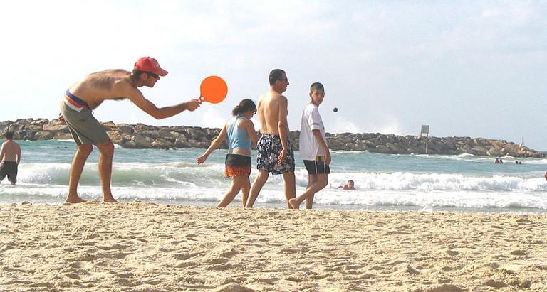 Playing matkot on an Israeli beach