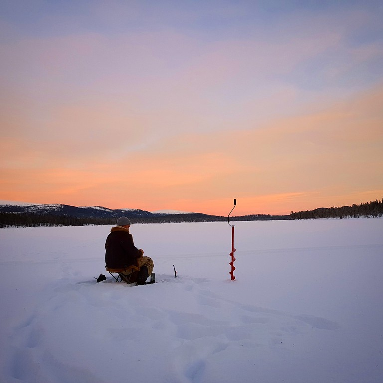 Ice fishing by sunset