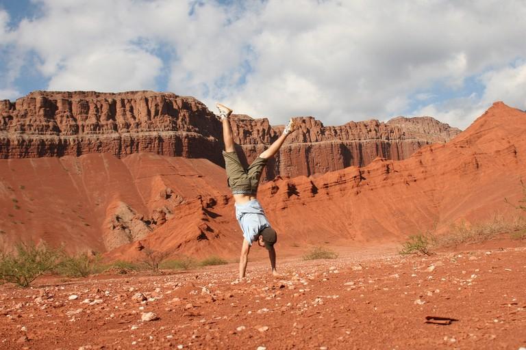 Traveler doing a handstand in Las Conchas, Salta, Argentina