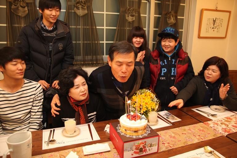 A family celebrates their grandfather's birthday