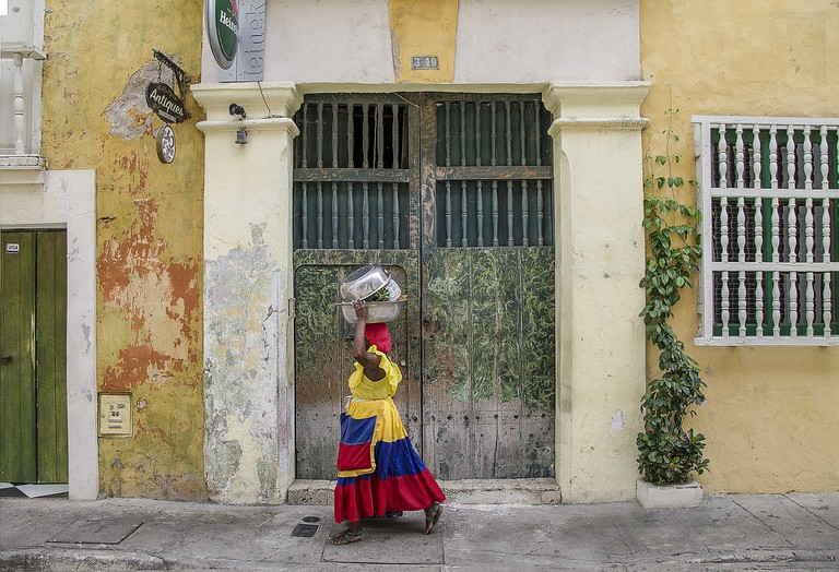 A palenquera walks through the streets of Cartagena
