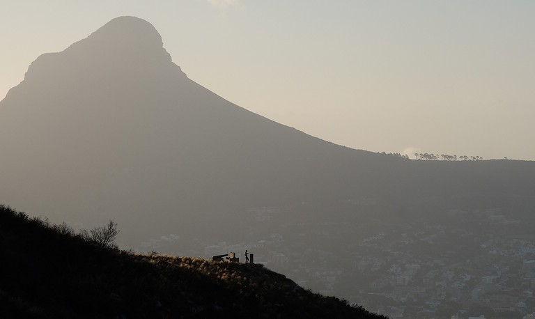Solo runner on Table Mountain dwarfed by Lion's Head