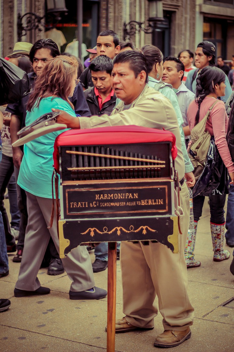 An organ grinder surrounded by the crowd