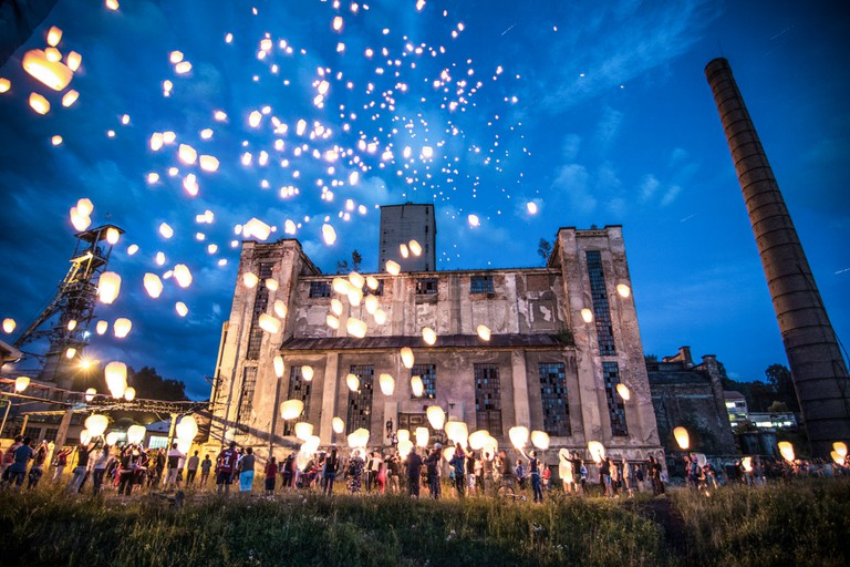 Chinese sky lanterns with Romanian poems are launched in front of one of Petrila Mine's historical buildings