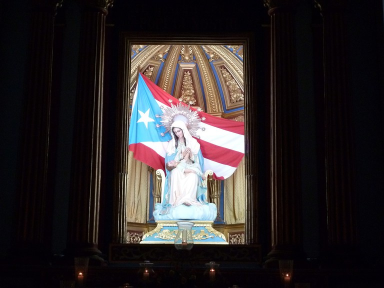 The Puerto Rican flag behind a Christian statue