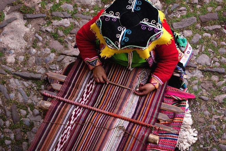 A Quechua-speaking local woman weaving a runner in Cusco, Peru