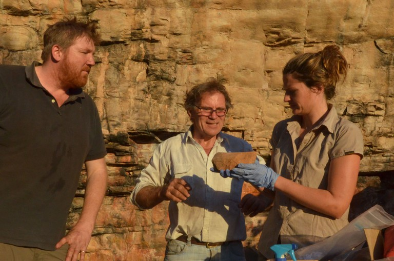 Team leader Chris Clarkson with Richard Fullagar and Elspeth Hayes examining a rare grindstone from the lowest layers of the excavation Courtesy