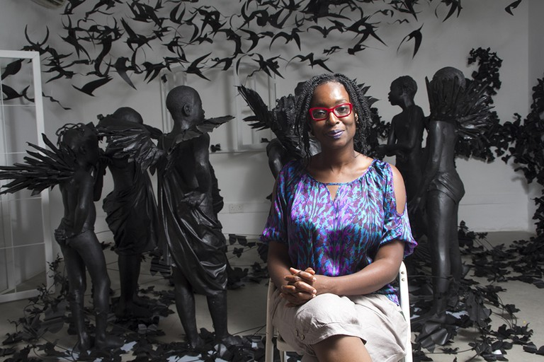 Peju Alatise, against a backdrop of her Flying Girls installation