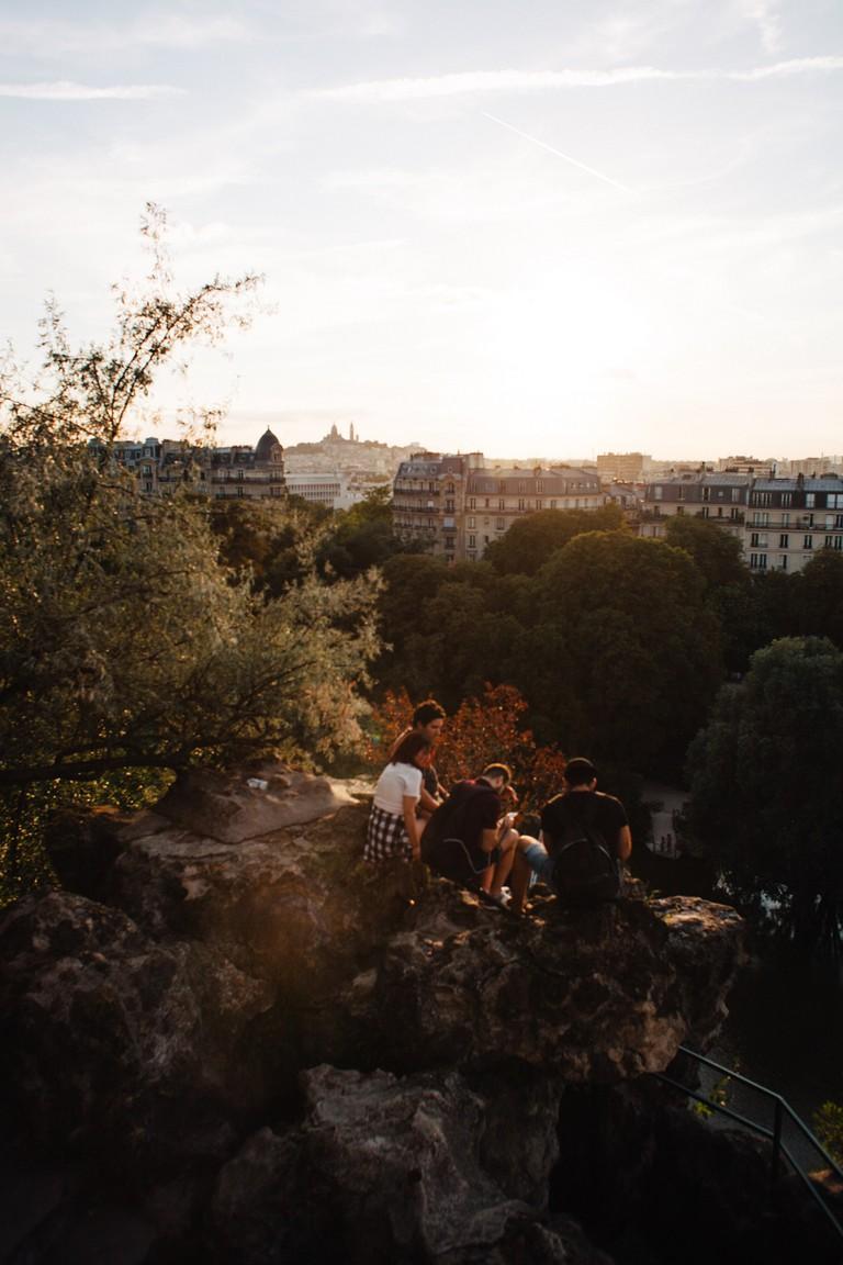 Group picnic on rocks at Parc des Buttes Chaumont │© Kim Grant for Culture Trip