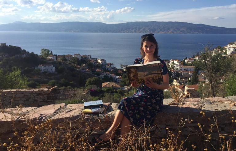 Katyuli Lloyd in Hydra, Greece, holding a copy of the book.