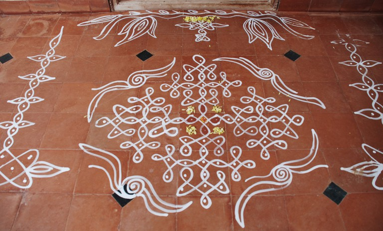An elaborate kolam design made in the porch area of a home