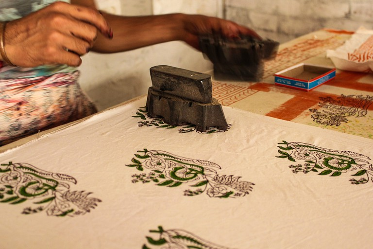 A worker dyes a fabric with block printing wood blocks