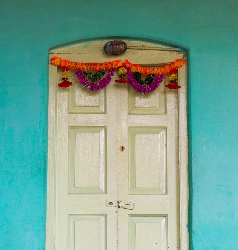 A colourful toran hanging from a door of an Indian home