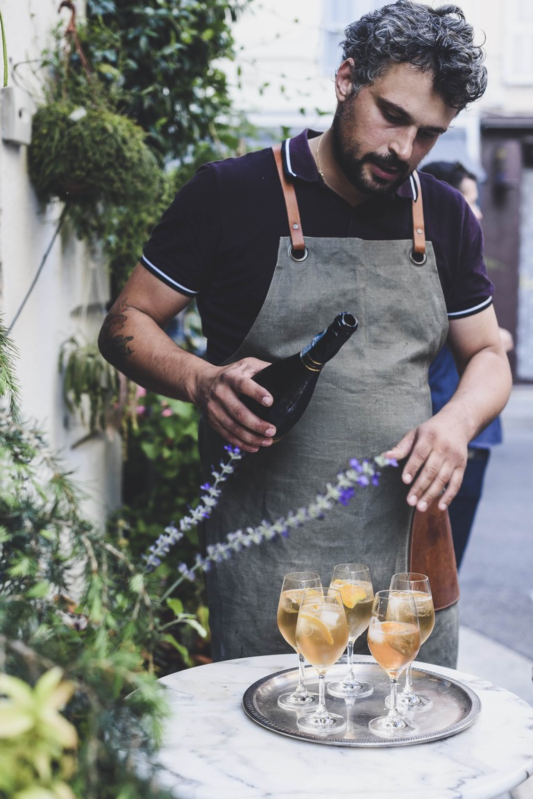 A sparkling apeeritif of vin d'orange and prosecco by sommelier Romain Forini adorned with agastache (hummingbird mint) petal ice cubes