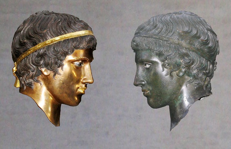 Juxtaposition of the colored reconstruction and the weathered original of a bronze head in the Munich exhibition