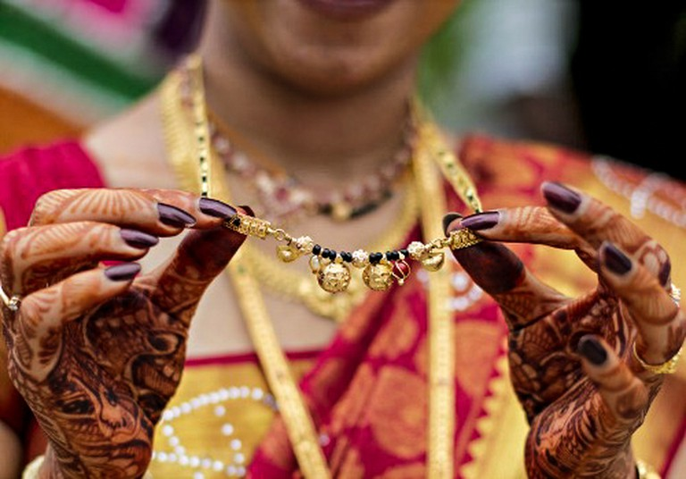 A bride shows off her mangalsutra after her wedding vows