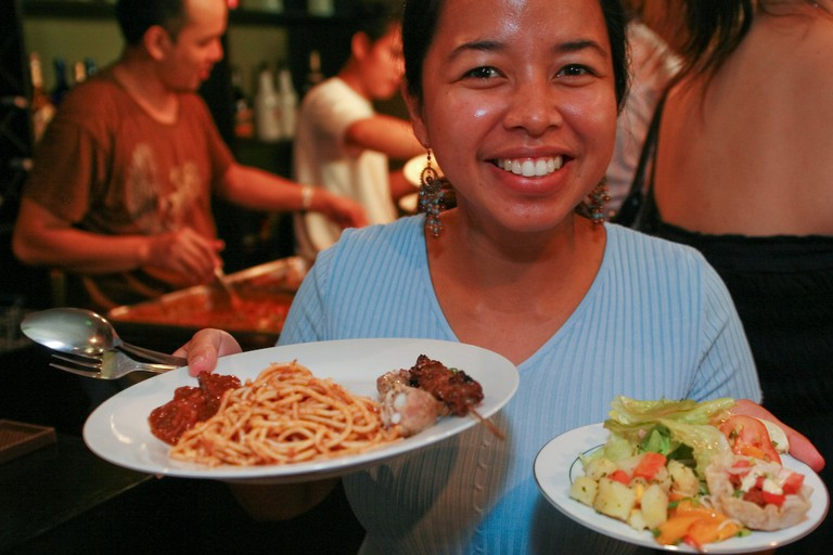 Happy Filipina holding plates of food