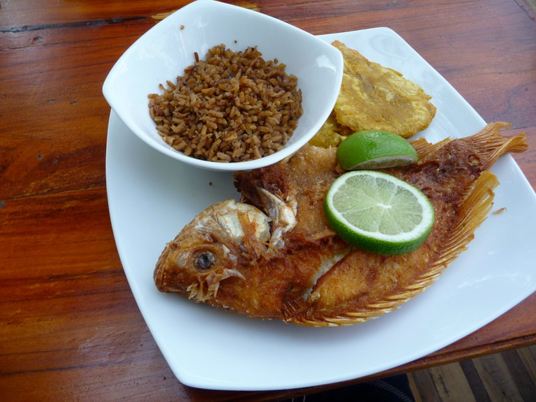 A delicious plate of Mojarra Frita, coconut rice, and patacones